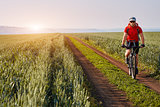 Young cyclist with mountain bicyclist on the path of the field in the countryside against sunrise.