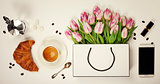 Top view of spring flowers, coffee, mobile phone, croissant  and