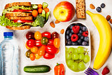 Healthy lunch box with sandwich and fresh vegetables, bottle of