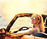 Young woman in cabriolet car near sea