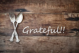 Antique Silverware and Grateful text over Wooden Background