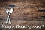 Antique Silverware and Happy Thanksgiving text over Wooden Backg