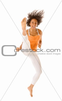 Sporty woman jumping and kicking