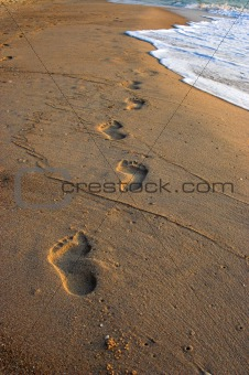 Footprints in the sand, at sunrise
