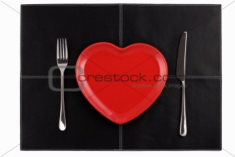 empty red heart plates with  knife and fork on black leather
