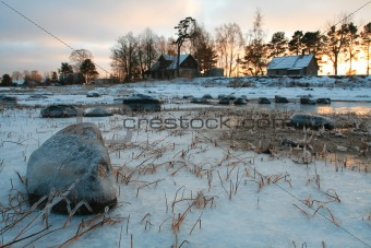 Houses next to icy meadow