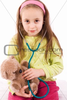 Adorable little girl playing doctor with a teddy bear