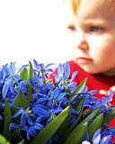 Little girl looks at a bouquet of snowdrops