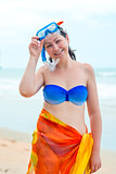 Happy girl in bikini near the sea on the beach in a mask for div