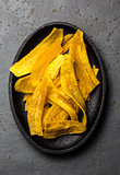 Healthy Homemade banana Plantain Chips on black plate, slate background