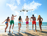 Group of friends run to the sea with an aircraft in the sky. Concept of travel and summer