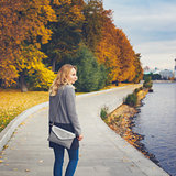 Woman walking in autumn park near river