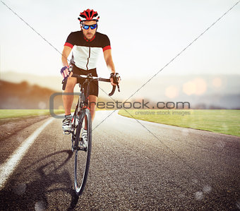 Cyclist racing on the road at sunset