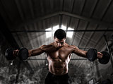 Athletic man training biceps at the gym