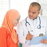 Medical doctor showing report to patient.