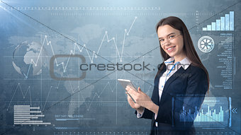 Beautiful woman in suit looking into a touch pad, painted studio background with copyspace. Business concept.