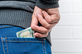 A man's hand pulls out dollars from the back pocket of jeans
