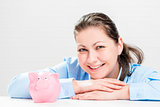 Happy young woman with a piggy bank pink