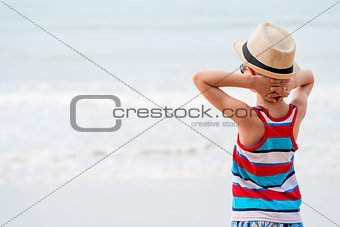 Boy in a hat and sunglasses admiring the sea