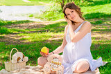 Young pregnant girl in a white sarafan on a plaid in a park at a