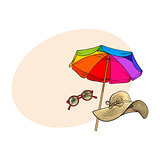 Straw hat with wide flaps, round sunglasses and beach umbrella