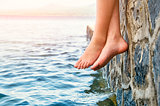 Bare girl's feet dangling from the stone jetty