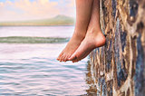 Young girl's feet dangling from the stone jetty