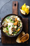 Seafood fish soup in clay bowls served with lemon and coriander. Top view, copy space