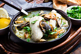 Seafood fish soup in clay bowls served with lemon and coriander. Closeup, copy space