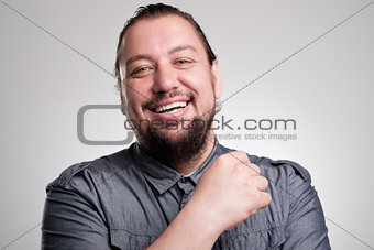 Portrait of laughing young man against grey wall. Happy guy smiling.