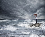 Businessman with umbrella during storm in the sea. Concept of crisis