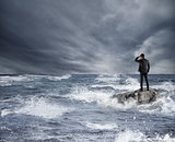 Businessman looking for the future during storm in the sea. Concept of economic crisis and problem