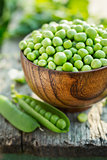 Fresh green peas in a bowl on old table