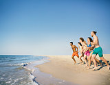 Group of friends run to the sea. Concept of summertime