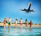Group of friends run in the sea with aircraft in the sky. Concept of summertime