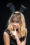 Sexy young blonde with ears hare on a black background
