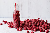 detox water in bottle with raspberry on white wooden background
