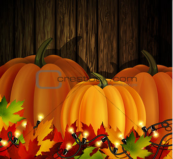Autumn leaves and pumpkins on wooden texture