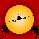Airplane silhouette over red sky and sun