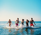 Group of friends run in the sea. Concept of summertime