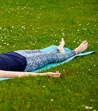 Girl doing yoga, meditating, Shavasana or corpse position in park on green grass
