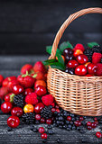 Berries mix in basket on dark wooden background