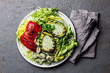 Vegetarian lettuce beans salad with grilled avocado and bell pepper. Top view