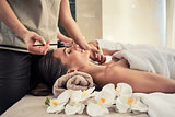 Relaxed woman lying down on massage bed during facial treatment