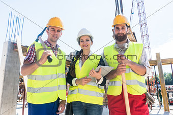 Portrait of confident colleagues posing during work break on construction site