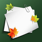 Paper sheets and maple autumn leaves.