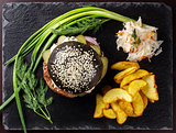 Black hamburger with onions and cucumbers on stone table with black background.