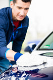 Hard-working man polishing car with white microfiber mitt