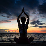 Fit woman sitting in lotus position while practicing yoga on the