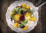 Healthy Beet Salad with red, white, golden beets, arugula, nuts, feta cheese on wooden background